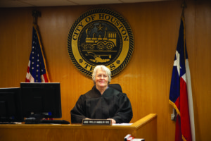 Phyllis Frye sits behind the bench in a judge's robe.